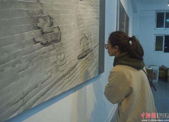 美术从业者细细观赏展览作品。 高媛媛 摄