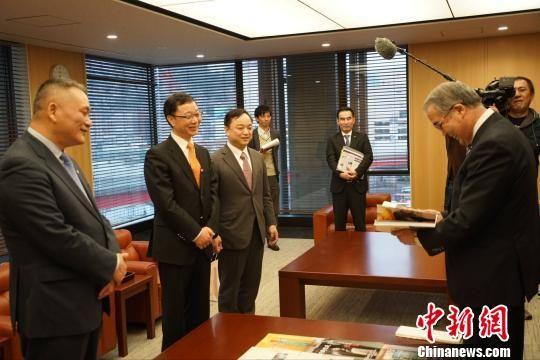 日本长崎县知事中村法道(右)观阅《印象长崎》。 刘可耕 摄