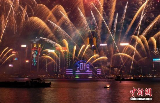 """2019年1月1日0时,历时10分钟的""""烟火音乐汇演在香港维多利亚港上空正式上演。伴随着悠扬的音乐,璀璨烟花在空中绽放,幻彩光束在空中闪耀,会展中心玻璃幕墙上出现巨型""""2019""""字样。中新社记者 张炜 摄"""