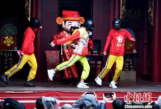 """参加巡游活动的""""抖音""""网红""""小铁头""""身穿红色的卡通财神卫衣,跳着时下流行的""""俄舞""""。 记者刘可耕 摄"""