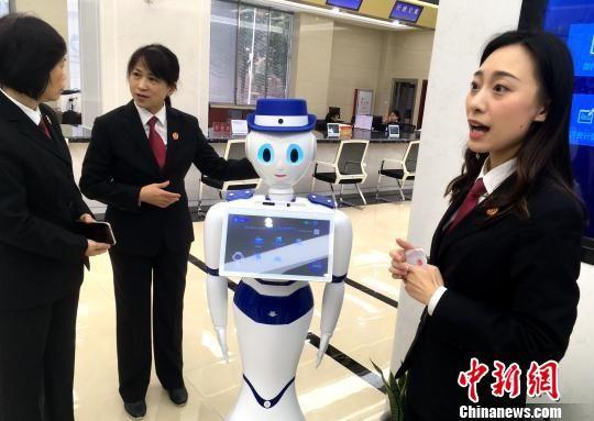 """诉讼服务中心工作人员介绍诉讼机器人""""小法""""。 张金川 摄"""