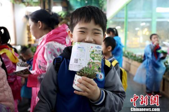 """参加植树活动的小朋友获赠""""植树节纪念证书""""和一盆多肉植物,开心不已。 供图"""