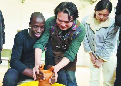 邱鹏(中)指导南非德班理工孔子学院的学生练习拉坯。范翠萍 摄