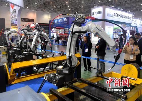 图为自动化设备吸引参观者。吕明 摄