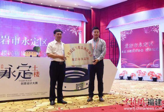 永定区长陈荣水为永定土楼民宿协会授牌。