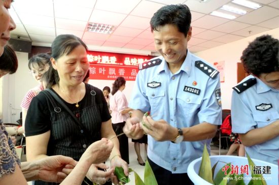 1 4日,福州东站派出所民警走进鹤林新城社区,与社会干部、工作人员和社区居民们一起包粽子,欢庆端午佳节。林坚 摄