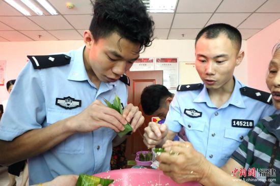 2在热情的社区居民阿姨的手把手指导下,民警们很快掌握了包粽子的方法与技巧,包出了自己的第一个、第二个粽子。林坚 摄