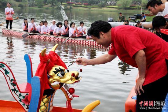 1全国首艘高校制造的传统木质龙舟在福大下水。图为该校党委书记陈永正为龙舟点睛。 福州大学 供图