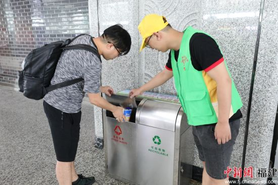志愿者正在引导旅客正确进行垃圾分类投放。南昌铁路局 供图