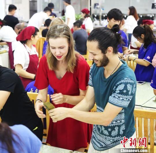 留学生对中国包粽子民俗饶有兴趣。供图 摄