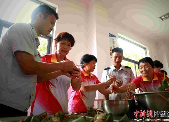 图为奶奶们手把手传授包粽子技巧。