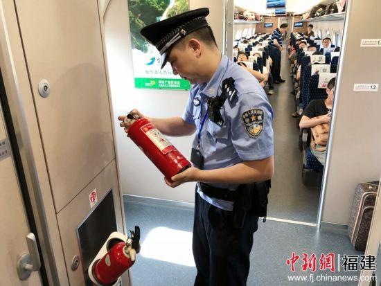 图为乘警检查列车垃圾箱等易发生火灾的场所