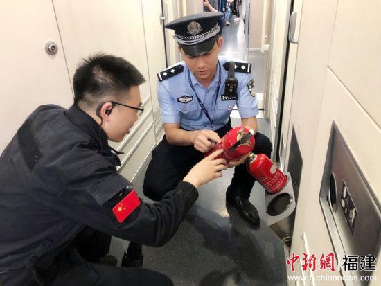 图为乘警向安全员讲解灭火器的使用方法