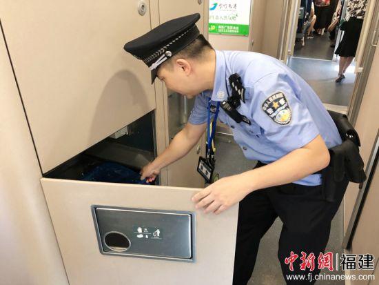 图为乘警检查列车配备的灭火器是否能正常使用