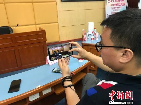 工作人员展示用5G手机观看庭审直播。 黄咏绸 摄