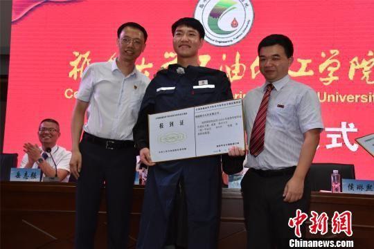 毕业典礼上举行校企人才交接仪式,为就业的学生发放工作证和工作服。 陈龙山 摄