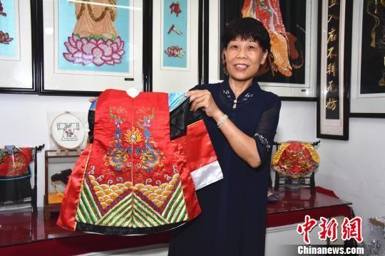 """闽南""""绣娘""""陈克忍展示用金苍绣技艺制成的木偶戏服。 陈龙山 摄"""