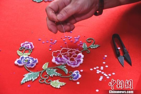 """在绣工的穿针引线下,花朵逐渐""""绽放""""在罗缎上。 陈龙山 摄"""