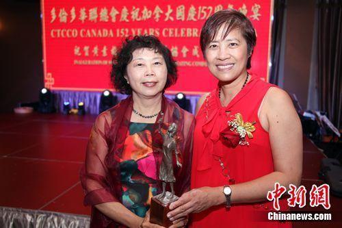 """图为黄素梅(右)在协会成立仪式上,将一尊微缩版""""慰安妇""""纪念雕像颁赠给在征集""""支持设立南京大屠杀纪念日""""民众签名中表现杰出的义工黄洁薇。 余瑞冬 摄"""