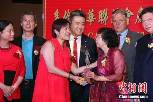 """图为黄素梅(左三)在协会成立仪式上,将一尊微缩版""""慰安妇""""纪念雕像颁赠给在征集""""支持设立南京大屠杀纪念日""""民众签名中表现杰出的义工黄洁薇。 余瑞冬 摄"""