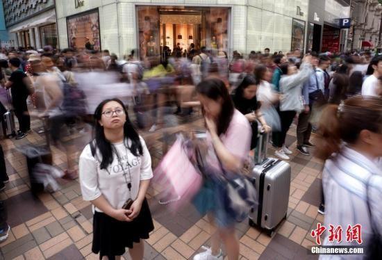 资料图:2019年五一假期期间,香港尖沙咀广东道一带的品牌店门前人潮涌动。中新社记者 张炜 摄