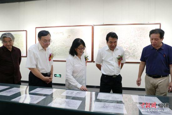 张梅芳教授(左3)正在为参展嘉宾们介绍画作。林坚 摄