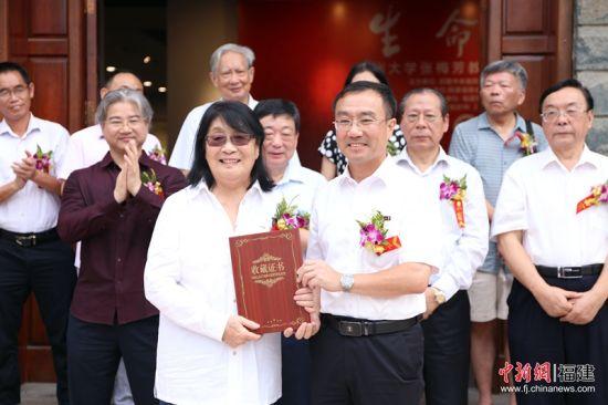 在开幕仪式上,福州大学党办、校办主任林键(图右)为张梅芳教授(图左)颁发了收藏证书。林坚 摄