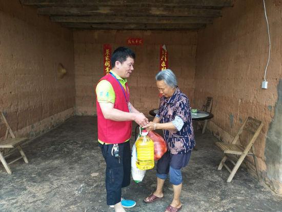 陈振富为孤寡老人送上米、油和苹果、香蕉等水果,并和老人聊天、谈心。