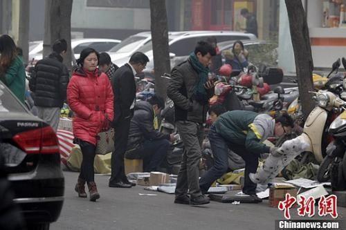 一家快递公司的员工蹲在马路边分发邮件,身边堆放着大量的包裹。 王中举 摄