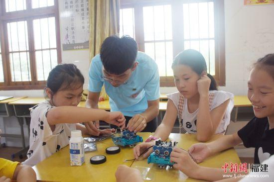 小朋友们认真学习如何操作机器人。福州大学 供图
