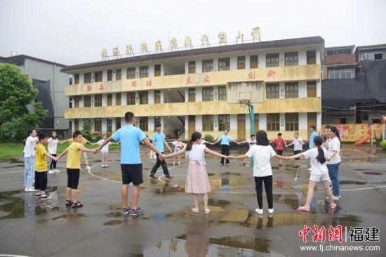 福州大学北斗实践队队员与当地小学生围成一圈玩耍。福州大学 供图