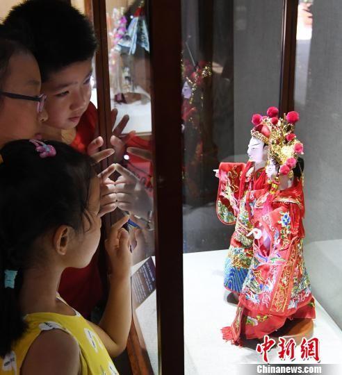 参展木偶头木雕作品《状元·夫人》吸引观展孩子们目光。记者刘可耕 摄