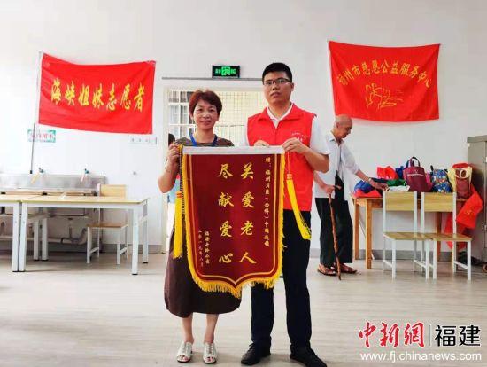 """福州市福海老龄公寓负责人赠予福州贝臣(齿科)中国连锁""""关爱老人 尽献爱心""""锦旗。"""
