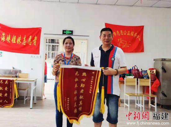 """福州市福海老龄公寓负责人赠予王友光""""热心助老献真情 无私奉献传美德""""锦旗。"""