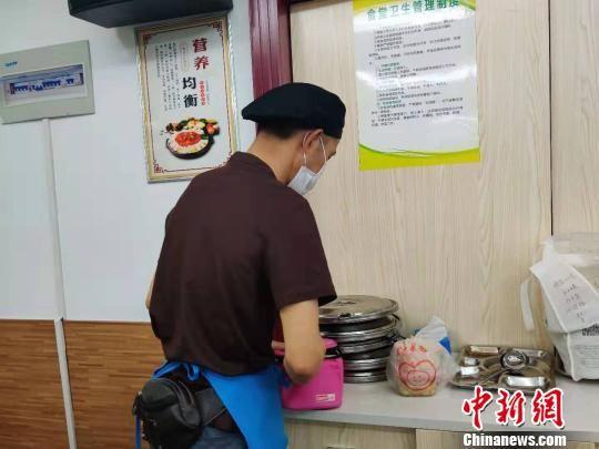 在食堂的分餐处,杨师傅已经开始忙碌起来,给需要送餐上门的老人备餐。 叶秋云 摄