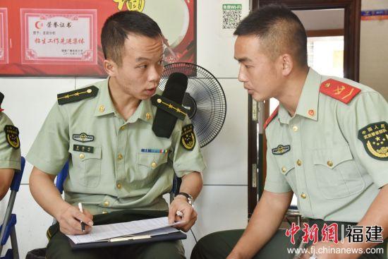 图为官兵相互间探讨报名事由。