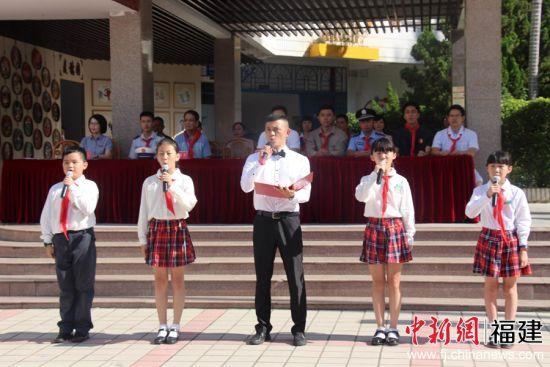 """新学期伊始,泉州市通政中心小学就以""""我和爸爸妈妈一起歌唱祖国""""为主题,联合师生和家长代表们一起上了别具意义的开学第一课。图为孩子们与家长代表齐声朗诵《我是中国人》"""
