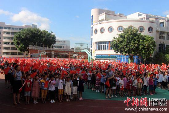 图为孩子家长挥舞国旗齐声高唱《歌唱祖国》。