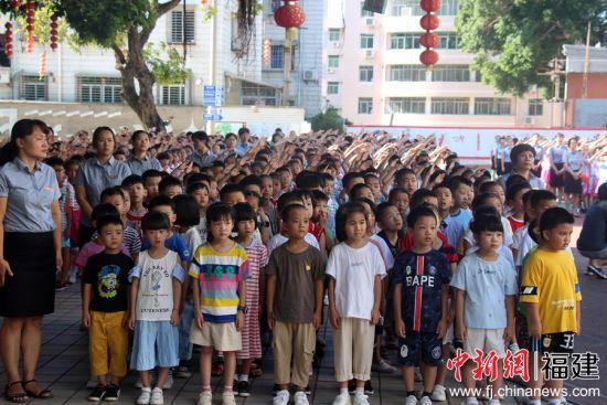 图为孩子们在升旗仪式上行礼。