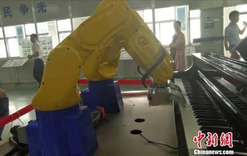 图为宏发股份工厂内,机器人在弹钢琴。 谢艺观 摄