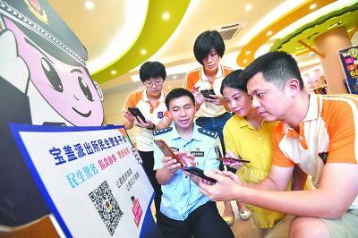 民警在为嘉育幼儿园安装二维码门牌,并指导如何使用民生警务平台。
