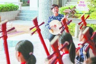 图为近日,锦歌非遗传承人王素华在教授孩子锦歌弹唱。