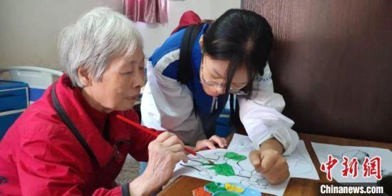护理学院的志愿者们陪公寓老人绘画。供图
