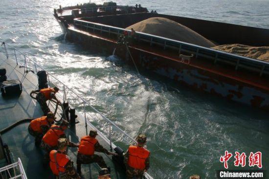 10日,福建莆田海警局在莆田南日岛附近海域连续查获2起非法盗采海砂案。图为海警执法人员靠帮嫌疑船舶。 李伟凡 摄