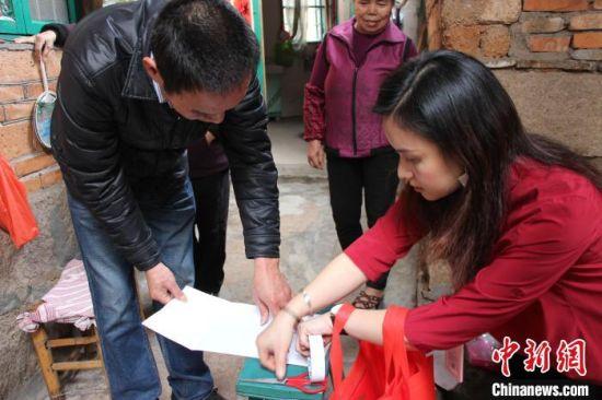 一位台湾社工协助福州市马尾区亭江镇东岐村村民贴春联。 王彦 摄