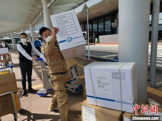 日本福建经济文化促进会千叶分会会长小张一郎等在搬运捐赠的防疫物资。 郑松波供图 摄