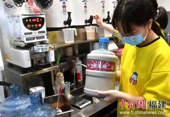 """3月13日,福建省福州市一奶茶店工作人员正在制作5升""""霸王桶""""奶茶。吕明 摄"""