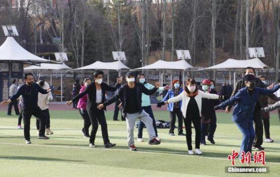 资料图:3月20日,西宁市户外体育场所已全部开放,市民在体育场上跳起锅庄。 中新社记者 马铭言 摄
