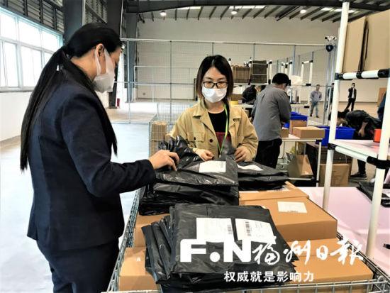 """工作人员整理跨境电商""""1210""""保税出口首票商品。记者 王玉萍 摄"""