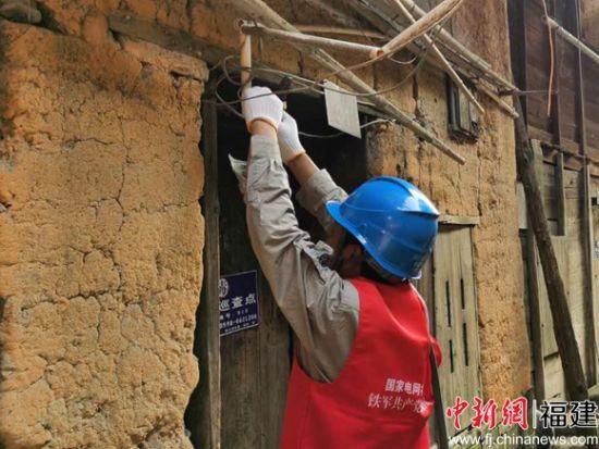 国网宁化县供电公司党员服务队为老人修理用电线路。吴娟 摄